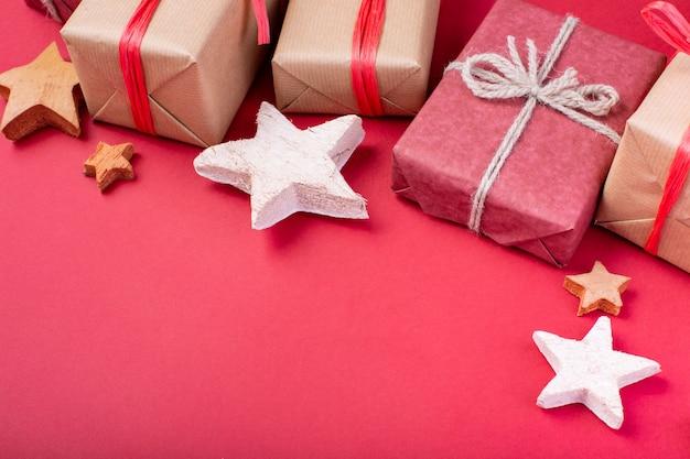 Decorações de natal vermelho, galhos de árvore do abeto com caixas de presente de brinquedos no vermelho