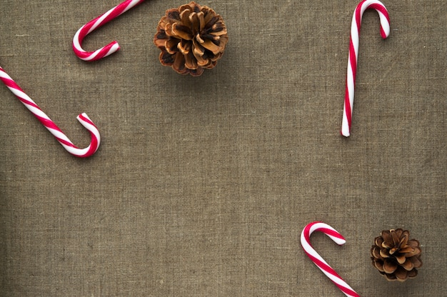 Decorações de natal: vista superior de bastões de doces e cones em fundo de tela de linho com espaço livre