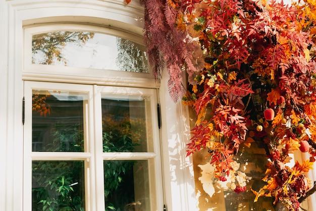 Decorações de outono folhas de laranja e flores ao redor das portas decoração de fachada