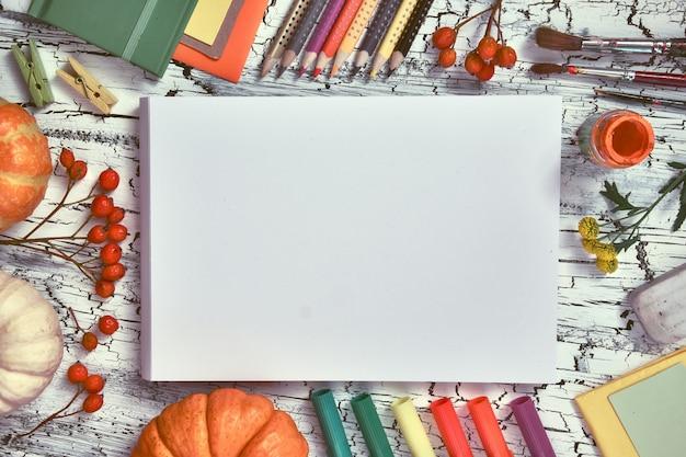 Decorações de outono, lápis, etiquetas de papel, tintas e pincéis, espaço