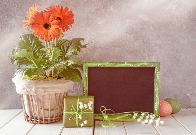 Decorações de páscoa e um quadro negro na mesa branca