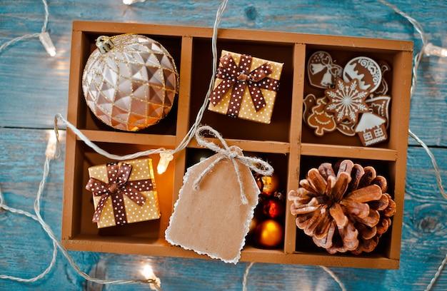 Decorações de presentes de natal estão em uma caixa sobre um fundo azul de madeira.