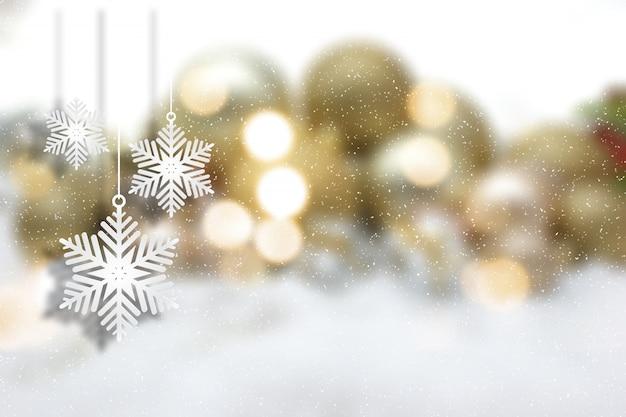 Decorações de suspensão do floco de neve do natal em um fundo defocussed