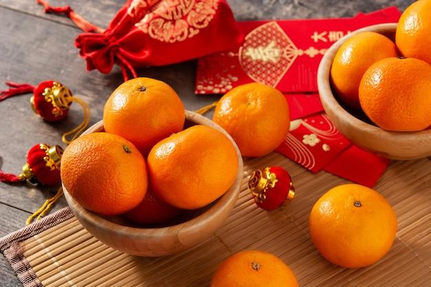 Decorações do festival de ano novo chinês e laranjas em fundo de madeira