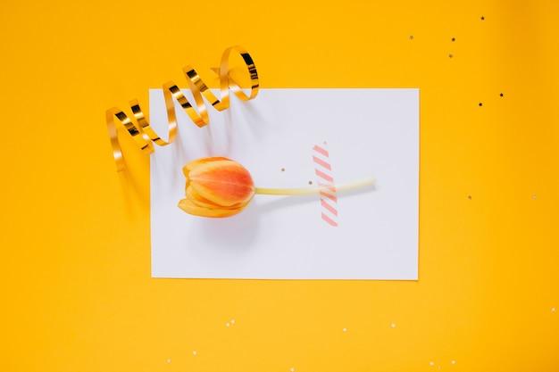 Decorações douradas da estrela do feriado e placa limpa branca com a tulipa vermelha para seu texto no fundo amarelo. conceito de planejamento.