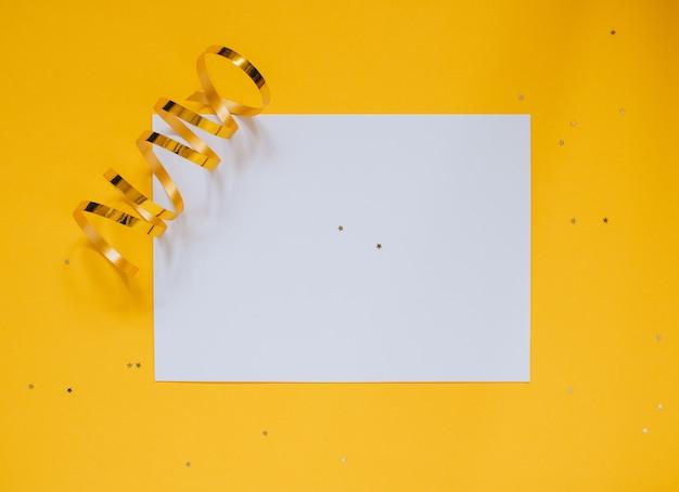 Decorações douradas da estrela do feriado e placa limpa branca para seu texto no fundo amarelo. conceito de planejamento.