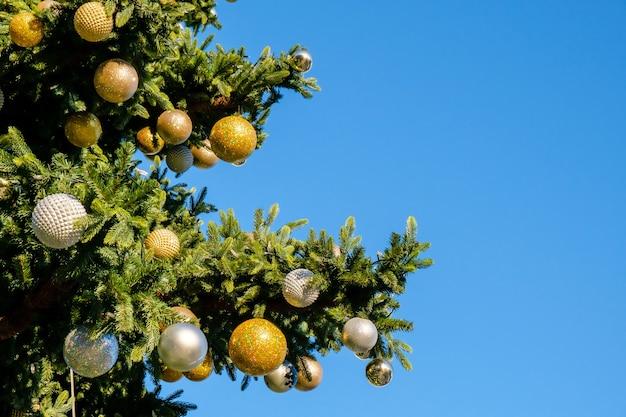 Decorações e festão nos galhos da falsa árvore de natal ao ar livre em um céu azul em um dia ensolarado de inverno.