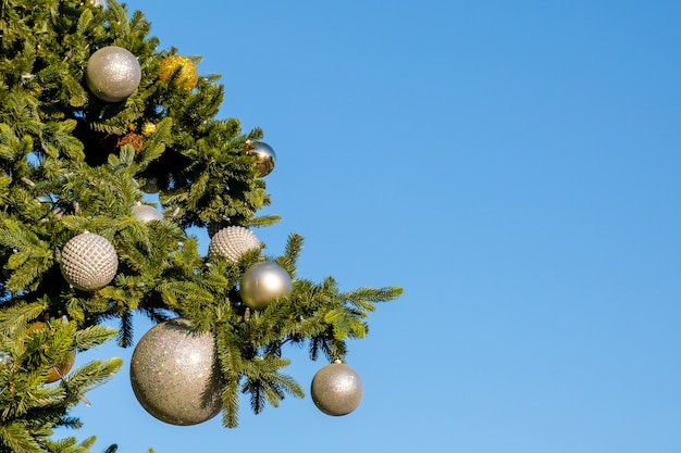 Decorações e festão nos galhos da falsa árvore de natal ao ar livre em um céu azul em um dia ensolarado de verão.