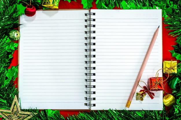 Decorações festivas de natal com caderno vazio e lápis sobre fundo de papel vermelho
