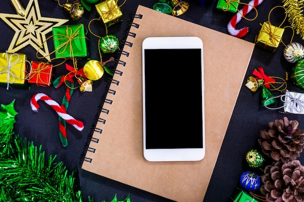 Decorações festivas de natal com smartphone vazio, caderno e lápis em papel preto bac