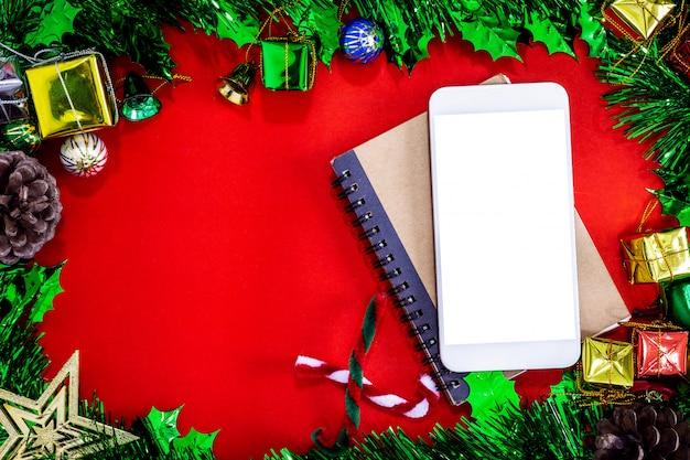 Decorações festivas de natal com smartphone vazio, caderno e lápis em papel vermelho backg