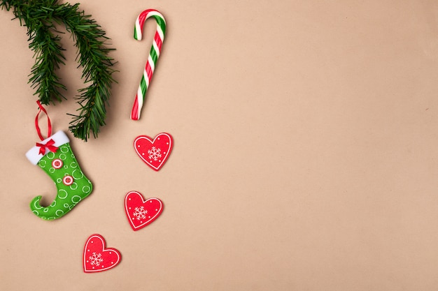 Decorações festivas, uma bota vermelho-verde para doces pendurados em um galho de árvore de natal, com um pirulito em forma de bengala, com um coração vermelho, sobre um fundo bege