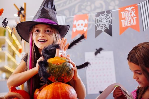 Decorações incríveis. linda garota engraçada e fofa usando chapéu de mago e preparando incríveis decorações de halloween
