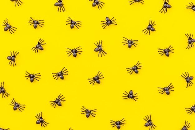 Decorações mínimas de halloween, composição com muitas aranhas pretas isoladas em fundo amarelo. conceito de doçura ou travessura de celebração de halloween. padrão de vista superior plana leiga.