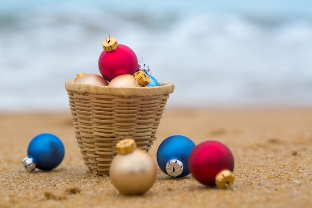 Decorações para árvores de natal em uma cesta em uma praia à beira-mar