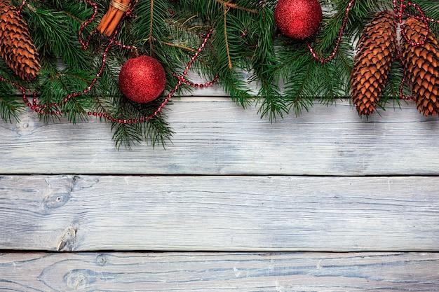 Decorações para árvores de natal em uma mesa de madeira com moldura de natal para parabéns