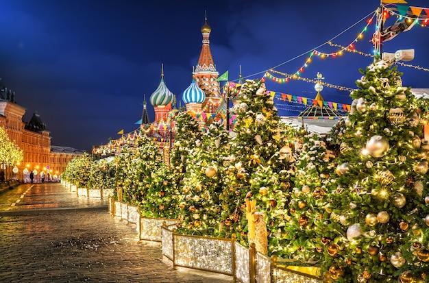 Decorações para árvores de natal na praça vermelha e as cúpulas da catedral de são basílio ao longe em uma noite de inverno