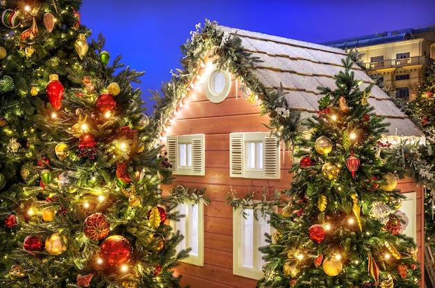 Decorações para árvores de natal perto de uma casa de madeira na praça manezhnaya em moscou em uma noite de inverno