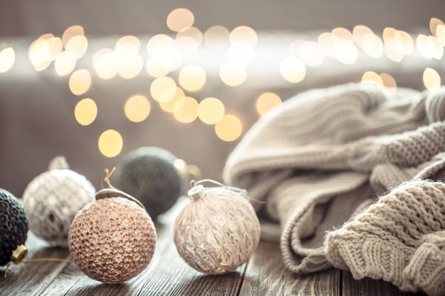 Decorações para árvores de natal sobre bokeh de luzes de natal em casa na mesa de madeira com camisola na parede e decorações.