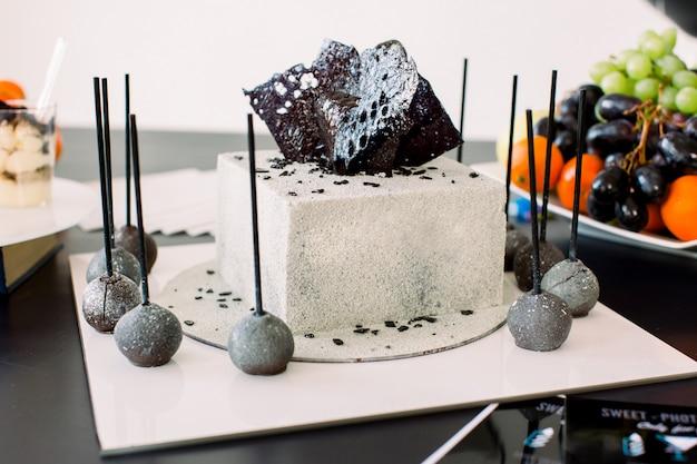 Decorações para festa de aniversário. elegante branco e preto decorado bolo de aniversário, deliciosas sobremesas e frutas frescas na mesa preta. conceito de festa de aniversário, bolo, sobremesas, barra de chocolate