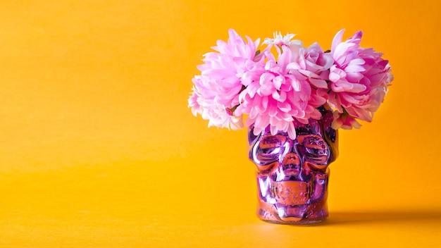 Decorações para o feriado dia de muertos. caveira decorativa com uma coroa de flores cor de rosa em um fundo laranja.