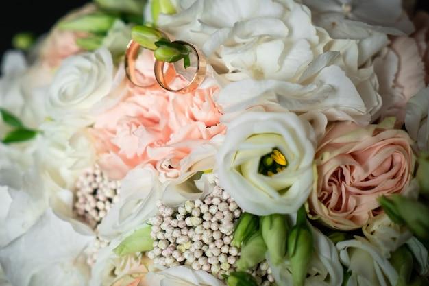 Decorações românticas, flores brancas para o feriado, alianças de casamento para a noiva
