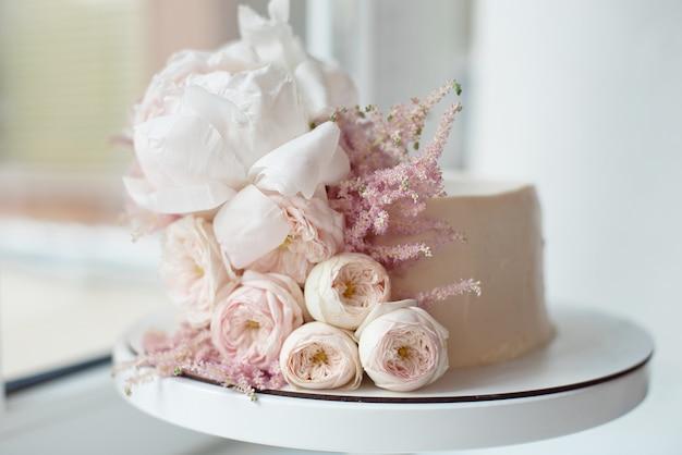 Decorado com flores frescas, bolo branco nu, um bolo elegante