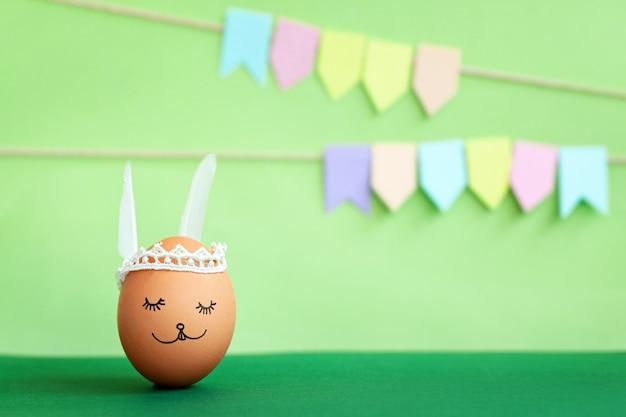 Decorado com ovo de páscoa e orelhas de coelhinho fofo com bandeiras coloridas sobre fundo verde
