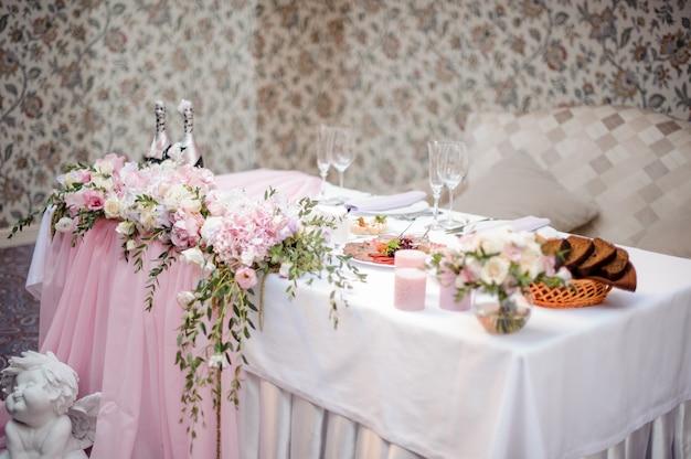 Decorado em tons de branco e rosa, mesa de buffet com pratos e champanhe