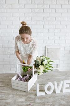 Decorador faz buquê de flores. jovem faz um enfeite de flores brancas em uma oficina. estúdio de luz florista com parede de tijolos no fundo.