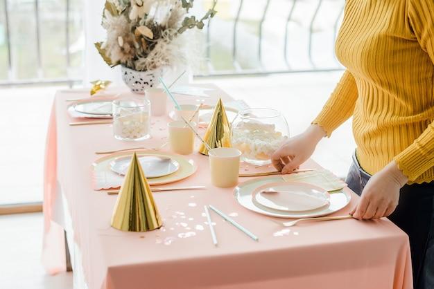 Decorador perto da mesa de festa em tons pastel com toalha rosa, pratos coloridos de papel, copos e talheres de ouro. decoração de festa de aniversário de menina, bonés festivos.