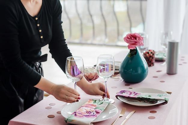 Decorador, servindo a mesa de festa em suaves cores rosa com toalha rosa, pratos brancos, copos de vinho, guardanapo floral. feliz aniversário ou chá de bebê para menina.