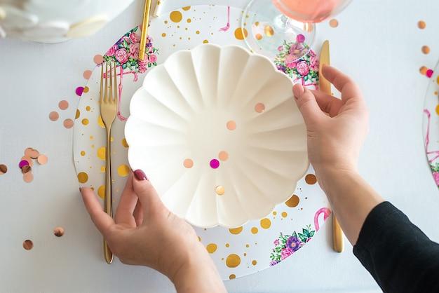 Decorador, servindo a mesa de festa nas cores brancas com belos pratos brancos, copos de vinho, talheres de ouro. feliz aniversário ou chá de bebê para menina. fechar-se