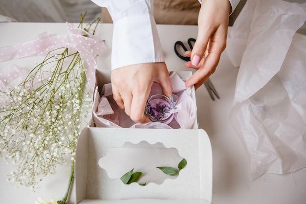 Decoradora coloca uma vela rosa decorativa em uma caixa de presente branca perto de flores