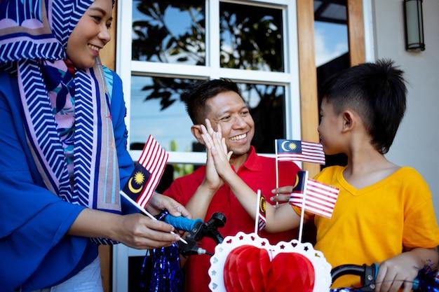 Decorando a bicicleta do filho com bandeira da malásia