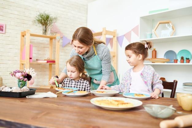 Decorando pastelaria com filhas pequenas