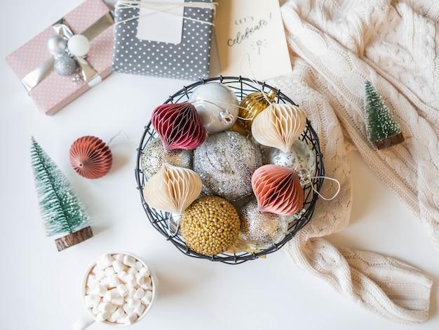 Decorar a cesta de vime metal com várias bolas de natal de ouro e prata, bebida quente na caneca e natal.