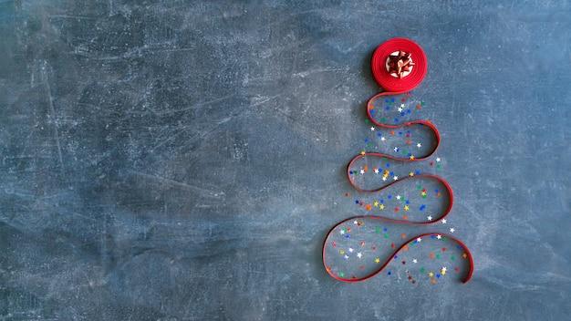 Decorativa árvore de natal feita de fita vermelha encaracolada e estrela de laço vermelho
