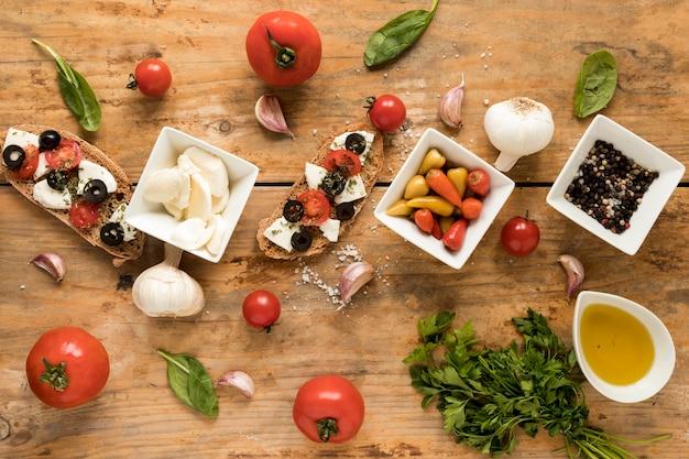 Decore bruschetta e ingrediente fresco para cozinhar na mesa marrom