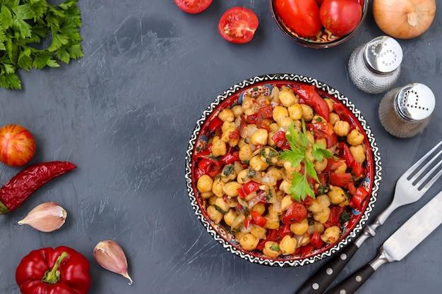 Decore o grão de bico com pimenta e tomate