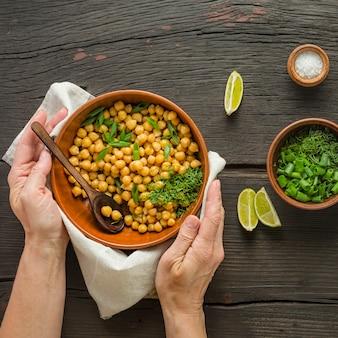 Decore o grão de bico. mulher serve grão de bico cozido em uma tigela sobre uma mesa de jantar. comida vegetariana
