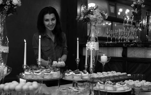 Decore uma mesa festiva com doces e uma variedade de salgadinhos doces, tendo como pano de fundo uma confeiteira