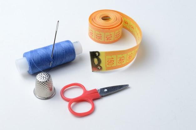 Dedal, agulha com carretel de linha, tesoura e fita métrica em um fundo branco .close-up.