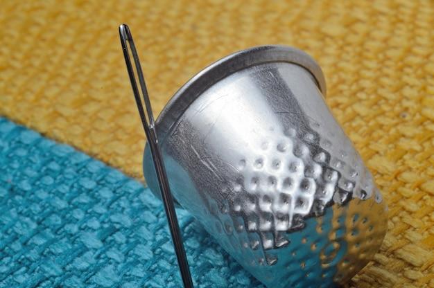 Dedal e agulha de costura em tecido amarelo-azulado. fechar-se.