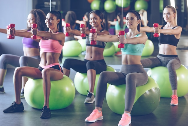 Dedicado ao fitness. jovens mulheres bonitas em roupas esportivas com corpos perfeitos se exercitando com halteres enquanto estão sentadas em bolas de fitness na academia