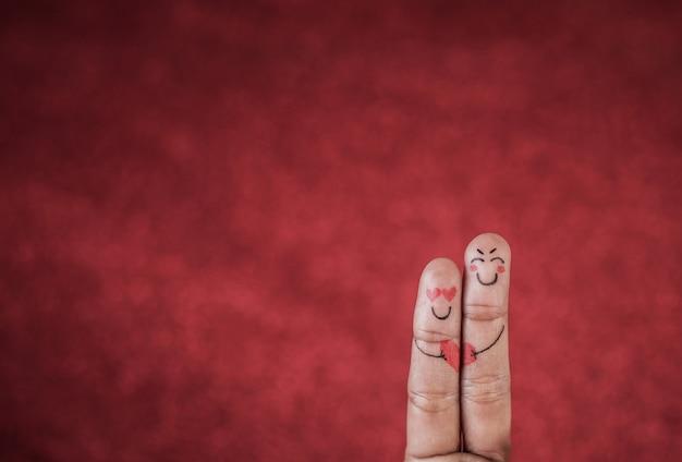 Dedo com emoção em fundo vermelho