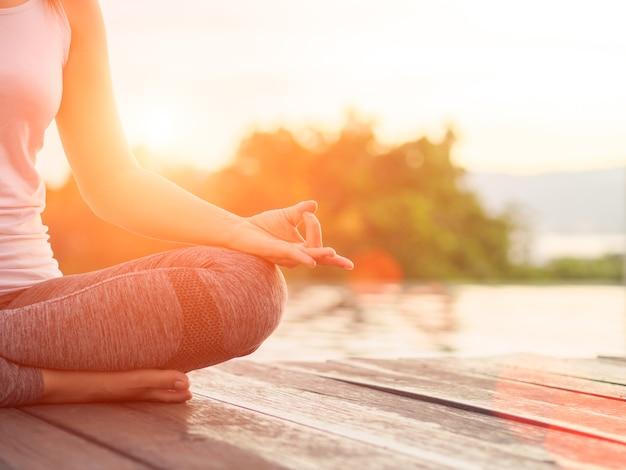 Dedo da ioga da mulher que actua nas mãos na frente do mar com fundo circunvizinho da natureza