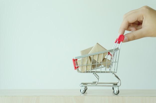 Dedo da mão da mulher empurrando o carrinho de compras pequeno com o conceito de compra online na internet.