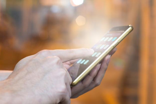 Dedo da mão homem apontando na tela smartphone no fundo da sala de controle