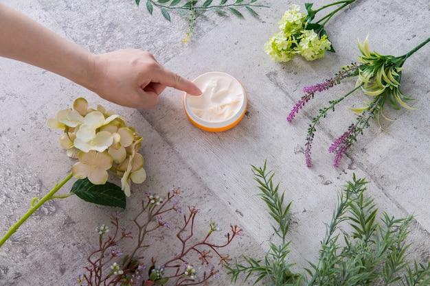 Dedo da mulher pegando creme de imagem orgânica, rodeado por vegetação